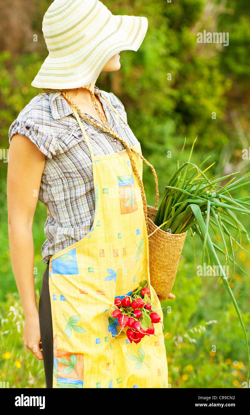 Happy woman gardener working on field, young female holding basket, girl growing organic green vegetables and fruits Stock Foto