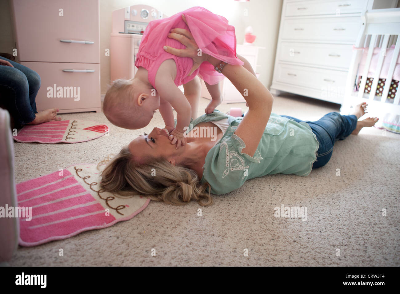 Mom holding her eleven month old girl up and playing in bedroom. Stock Foto