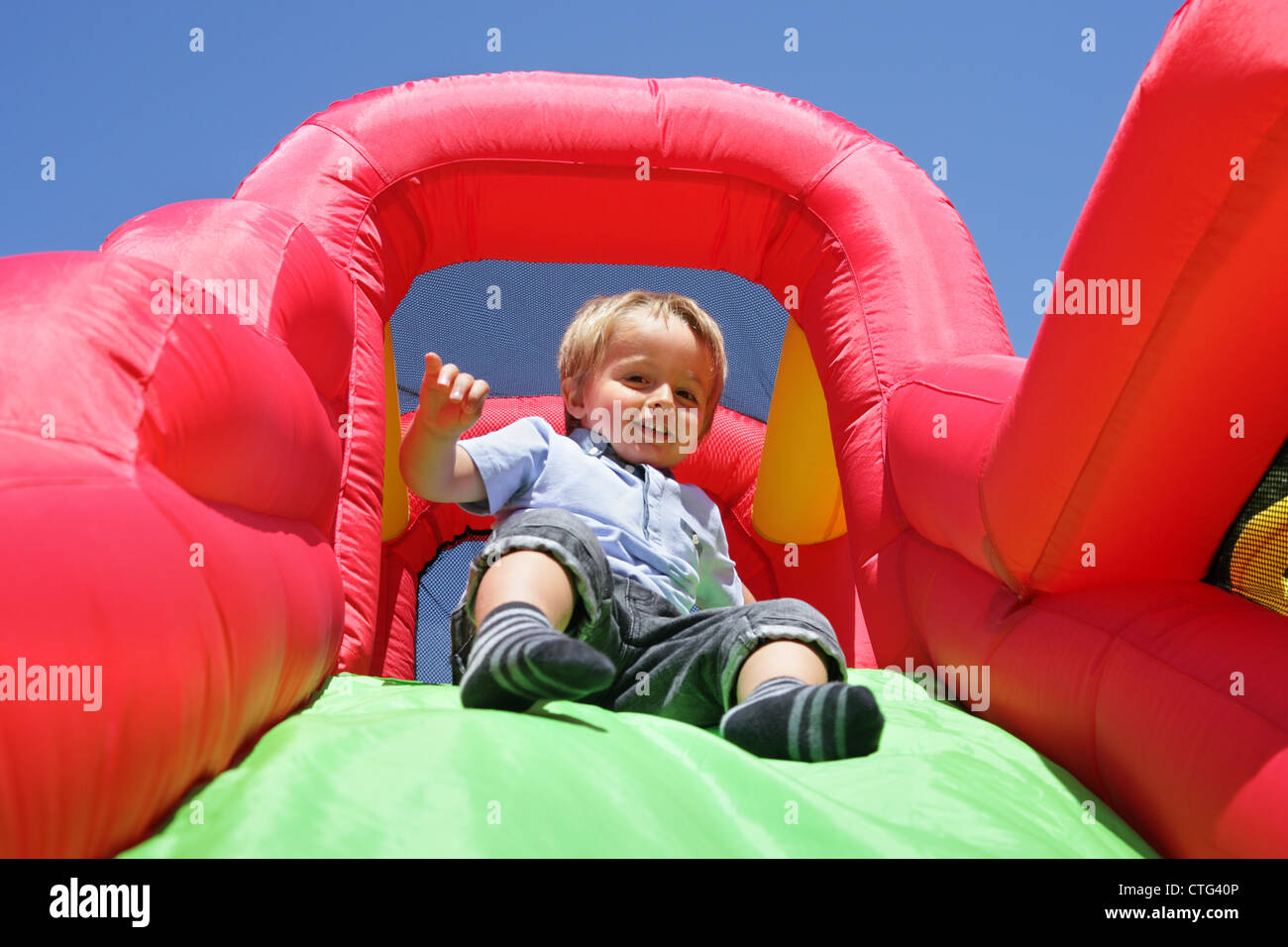 Child on inflatable bouncy castle slide Stock Foto