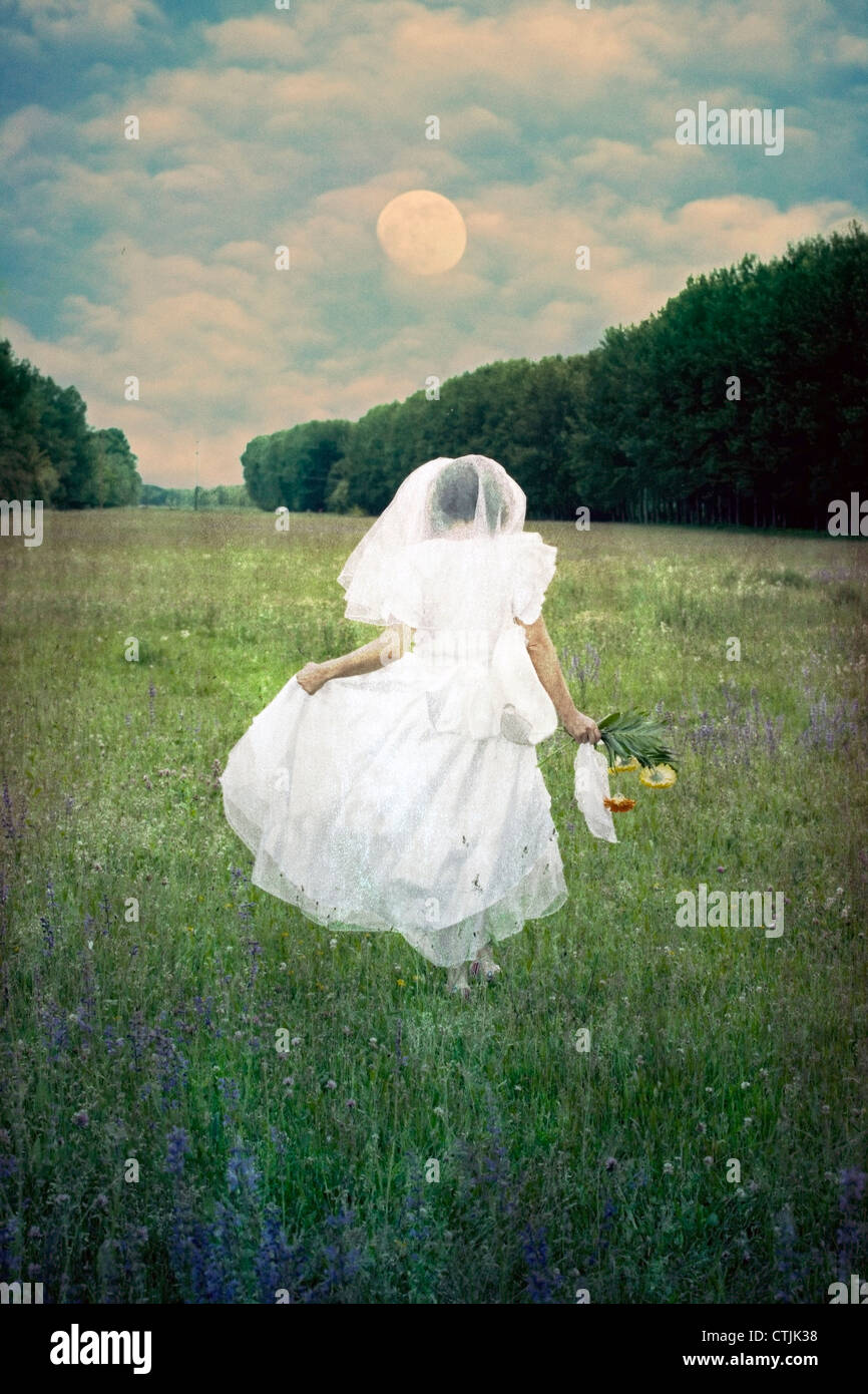 a woman is running with a wedding dress over a field of flowers Stock Foto