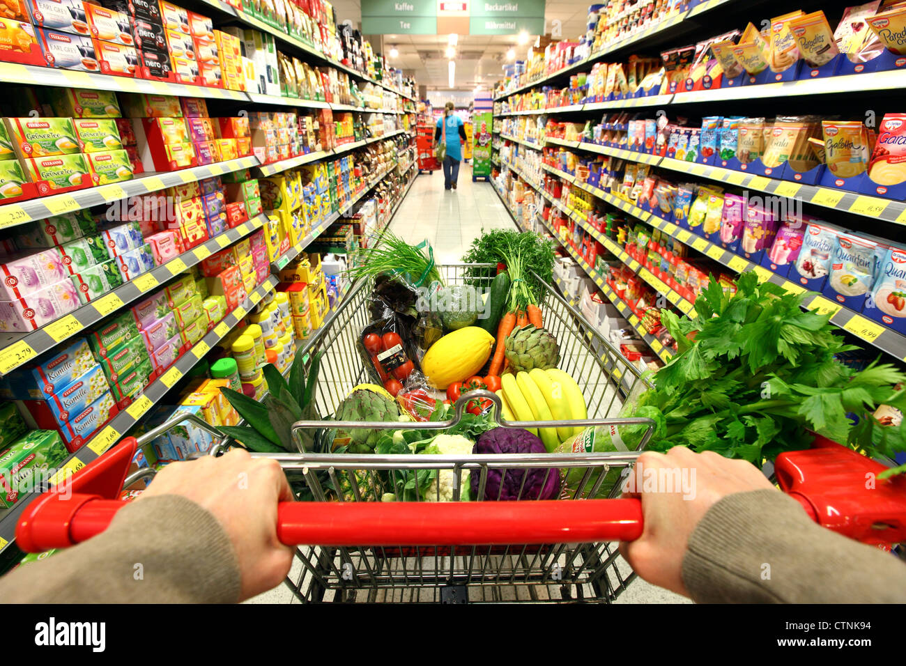 Food hall, full shopping trolley is pushed through a ...