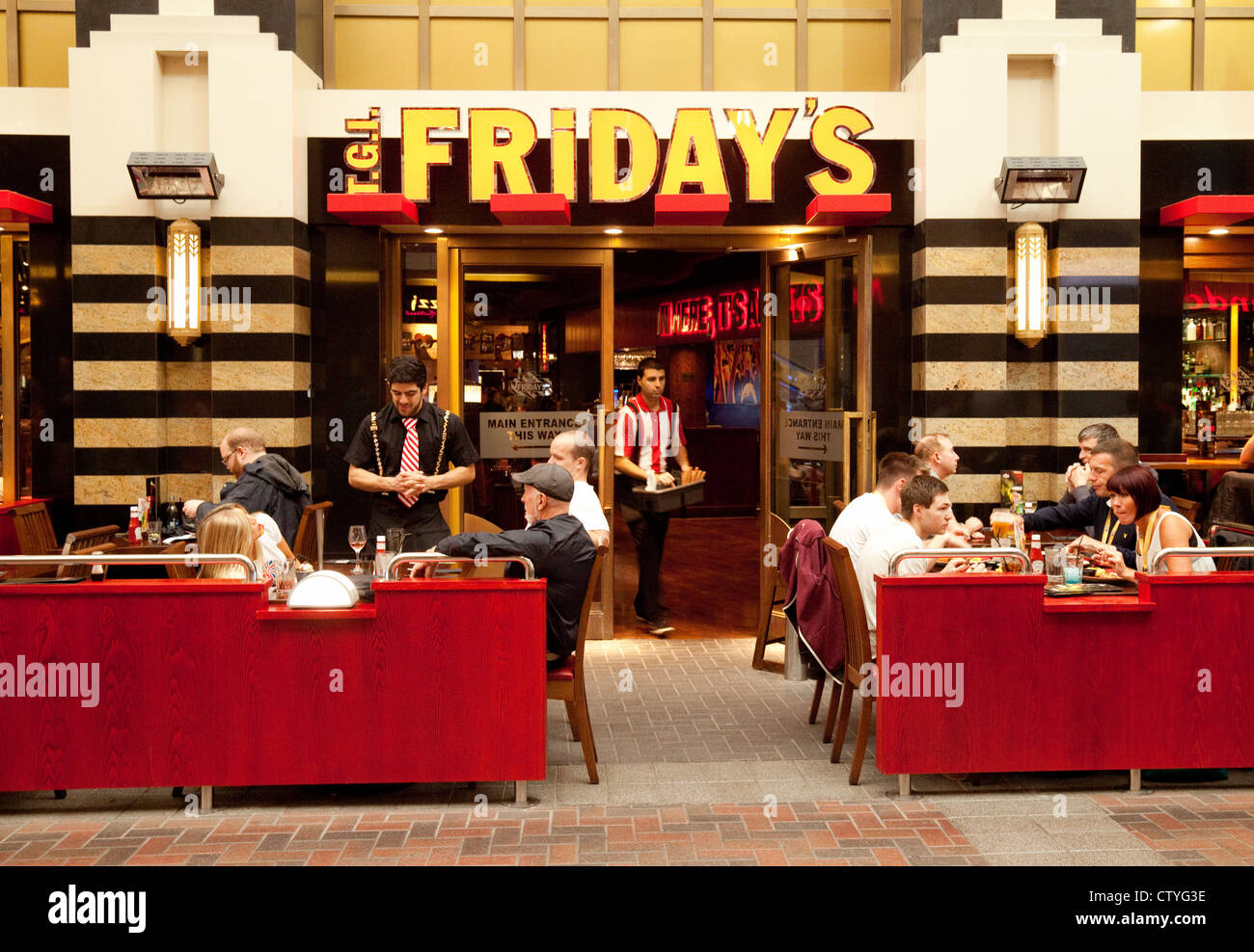waiter serving people eating at tgi fridays restaurant