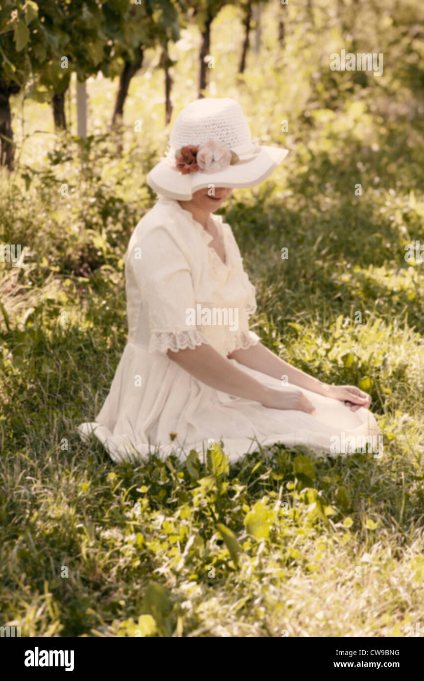 a woman in a white Victorian dress sitting on the grass between vines Stock Foto