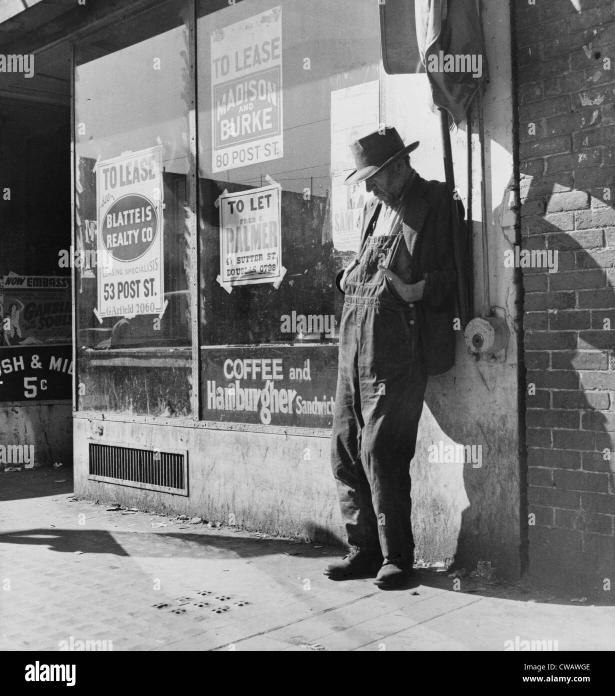 Lone man in farmer's overalls, on San Francisco's Skid Row at Howard Street. Ruined farmers from the Midwest added Stock Foto
