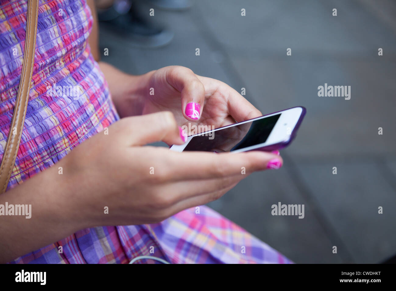 Young girl,with painted nails sends message on touch screen smart phone-close-up Stock Foto