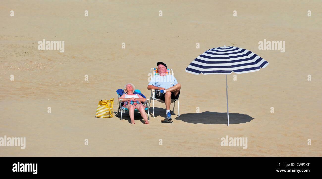 elderly-sunbathers-sleeping-in-beach-chairs-next-to-shadow-of-parasol-CWF2XT.jpg