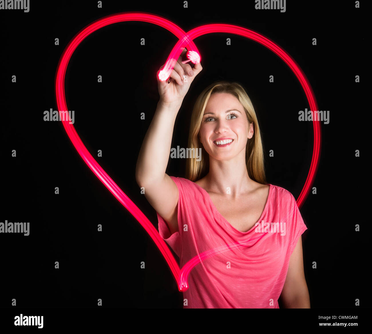 Woman drawing heart on black background Stock Foto