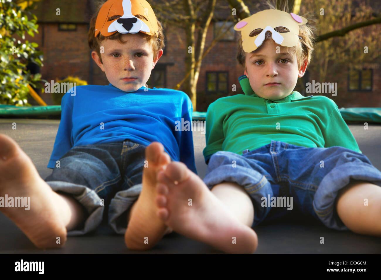 Two Boys Wearing Masks Lying on Trampoline Stock Foto