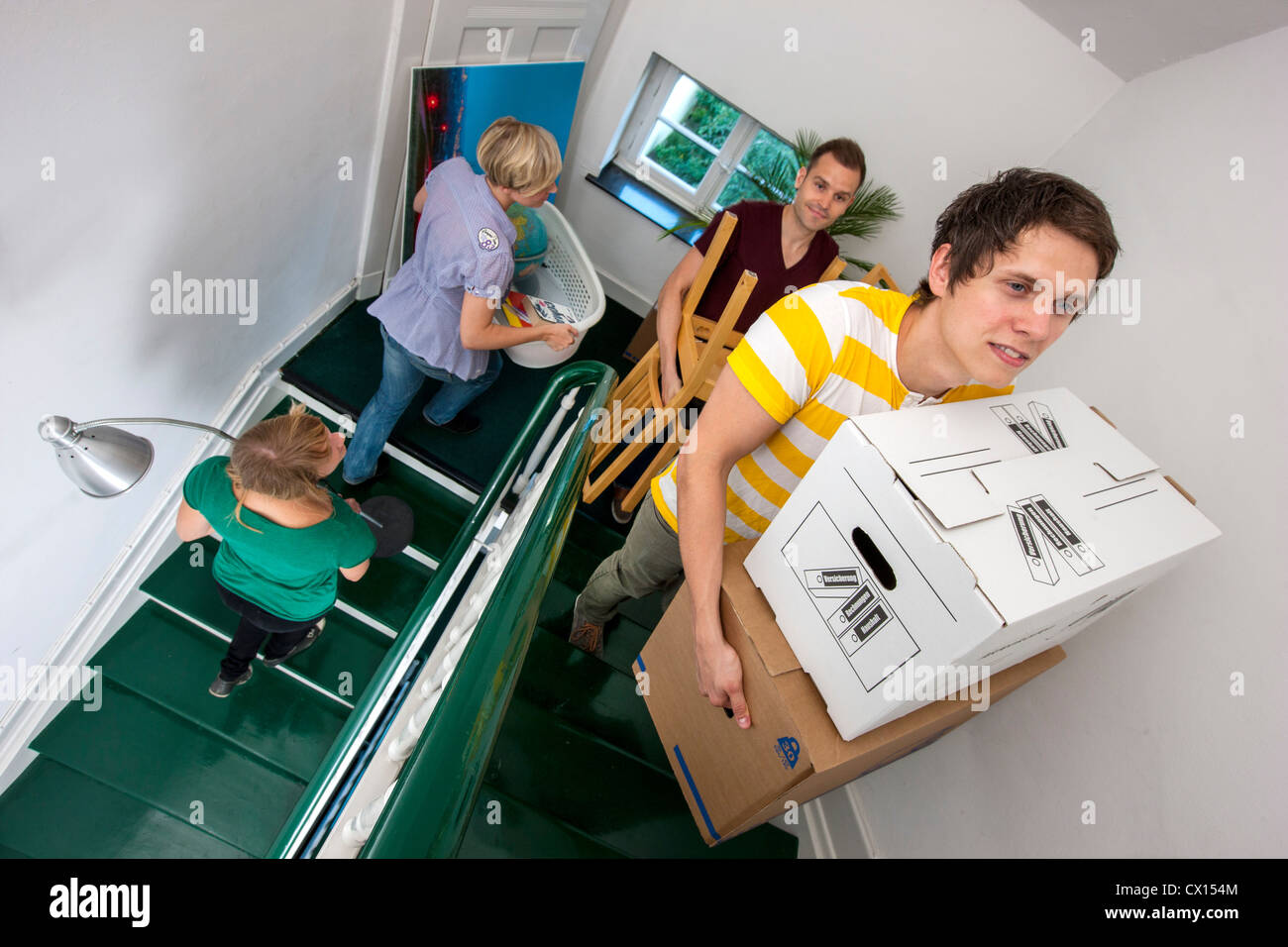 Young People Moving In To A New Apartment Friends Help Carrying