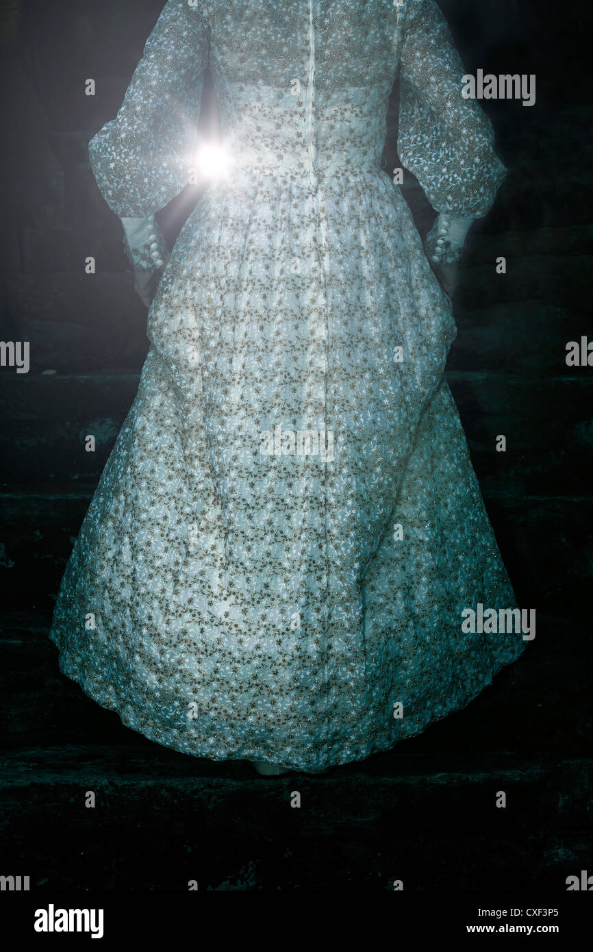 a woman in a period dress is walking up the stairs Stock Foto