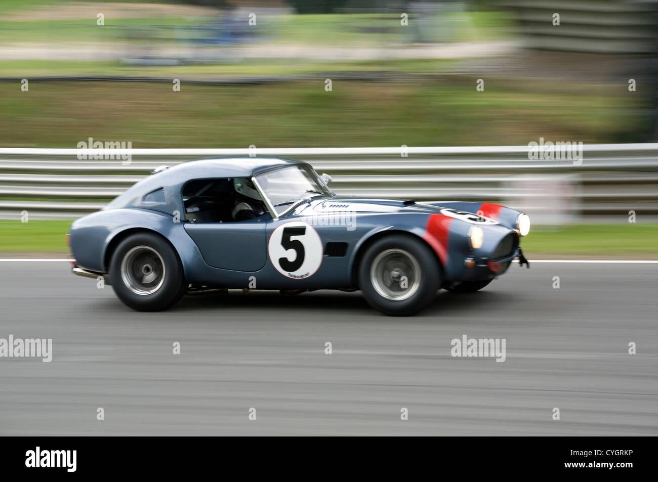 An Ac Cobra Hardtop Classic Racing Car Traveling Fast On A