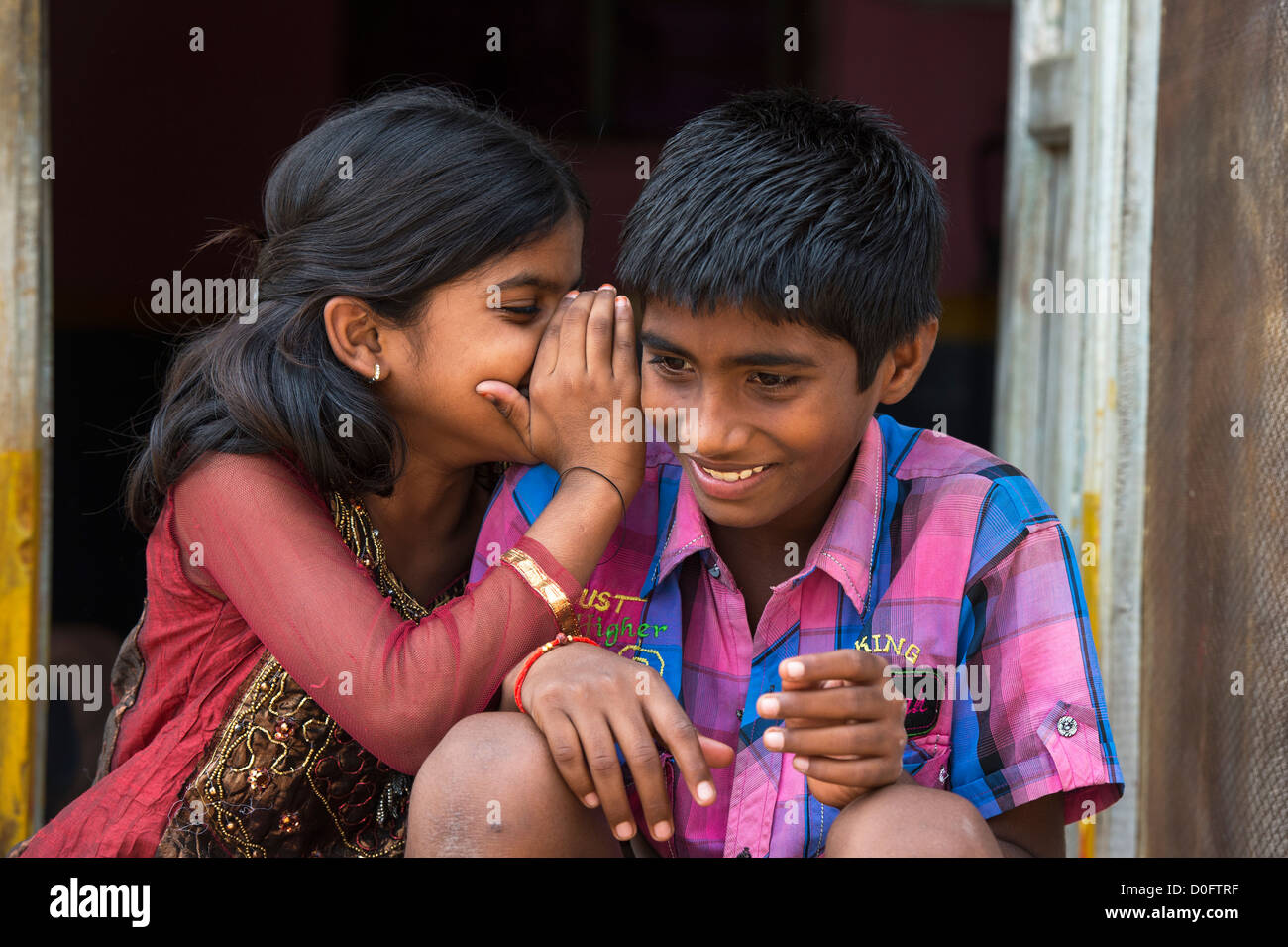 Young Indian girl whispering to a boy outside their rural Indian viilage home. Andhra Pradesh, India Stock Foto