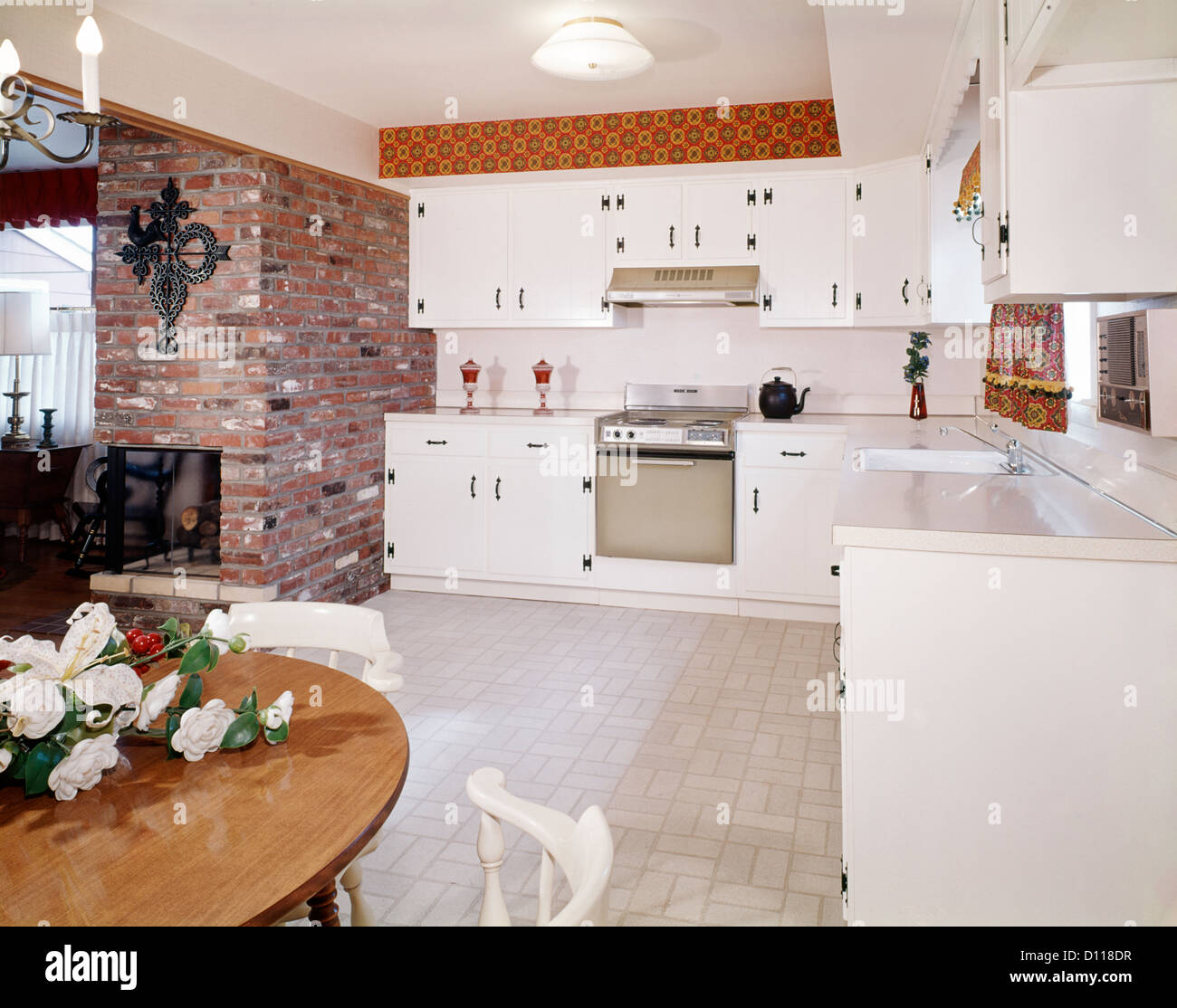 1960s KITCHEN INTERIOR WITH BRICK WALL AND WHITE COUNTRY CABINETS Stock Photo, Royalty Free