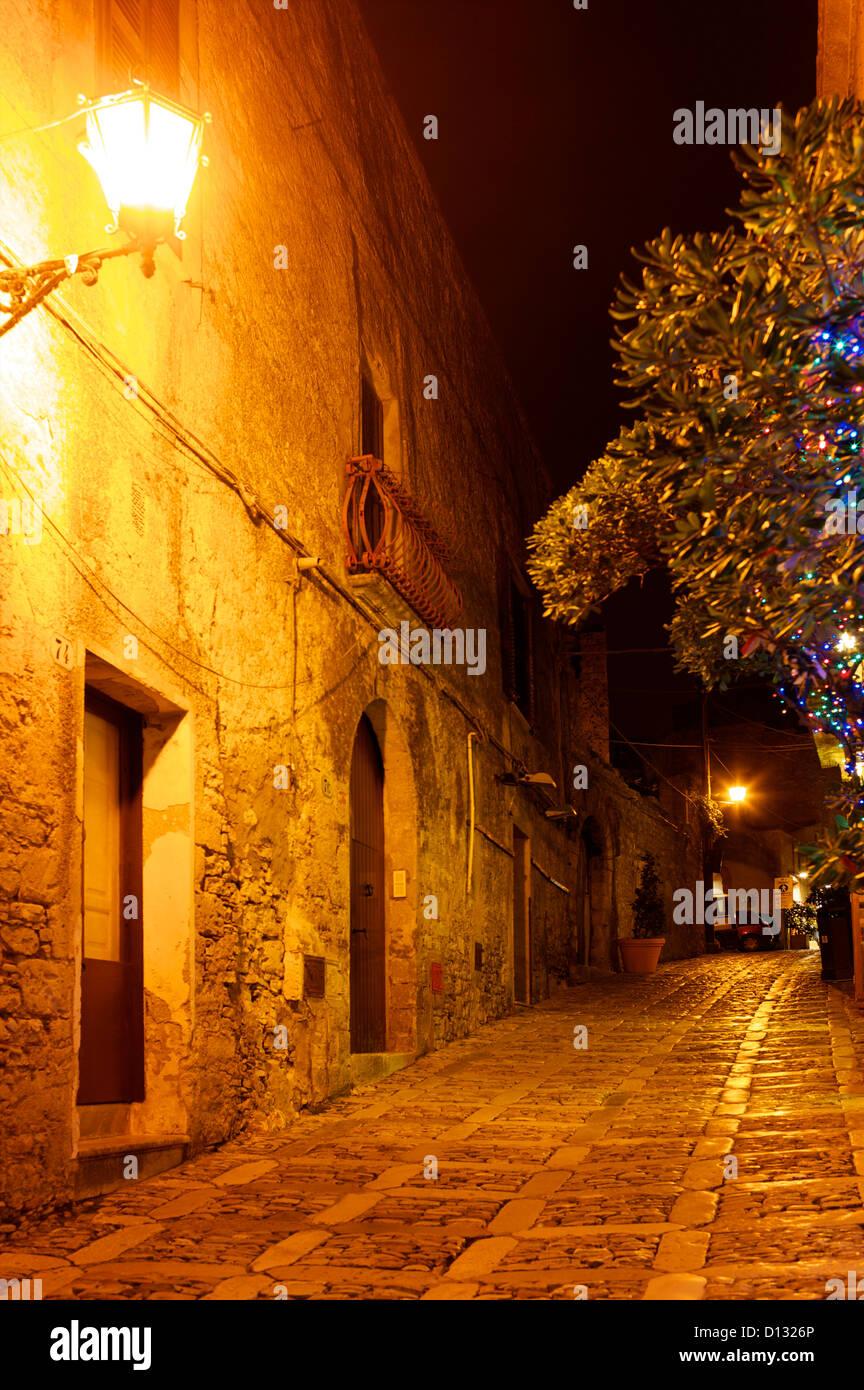 Cobblestone street illuminated by light at night. Stock Foto