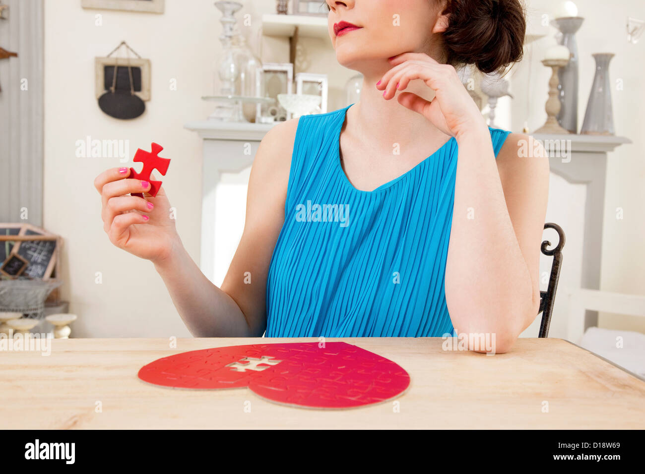 Woman doing heart shaped jigsaw puzzle holding piece Stock Foto