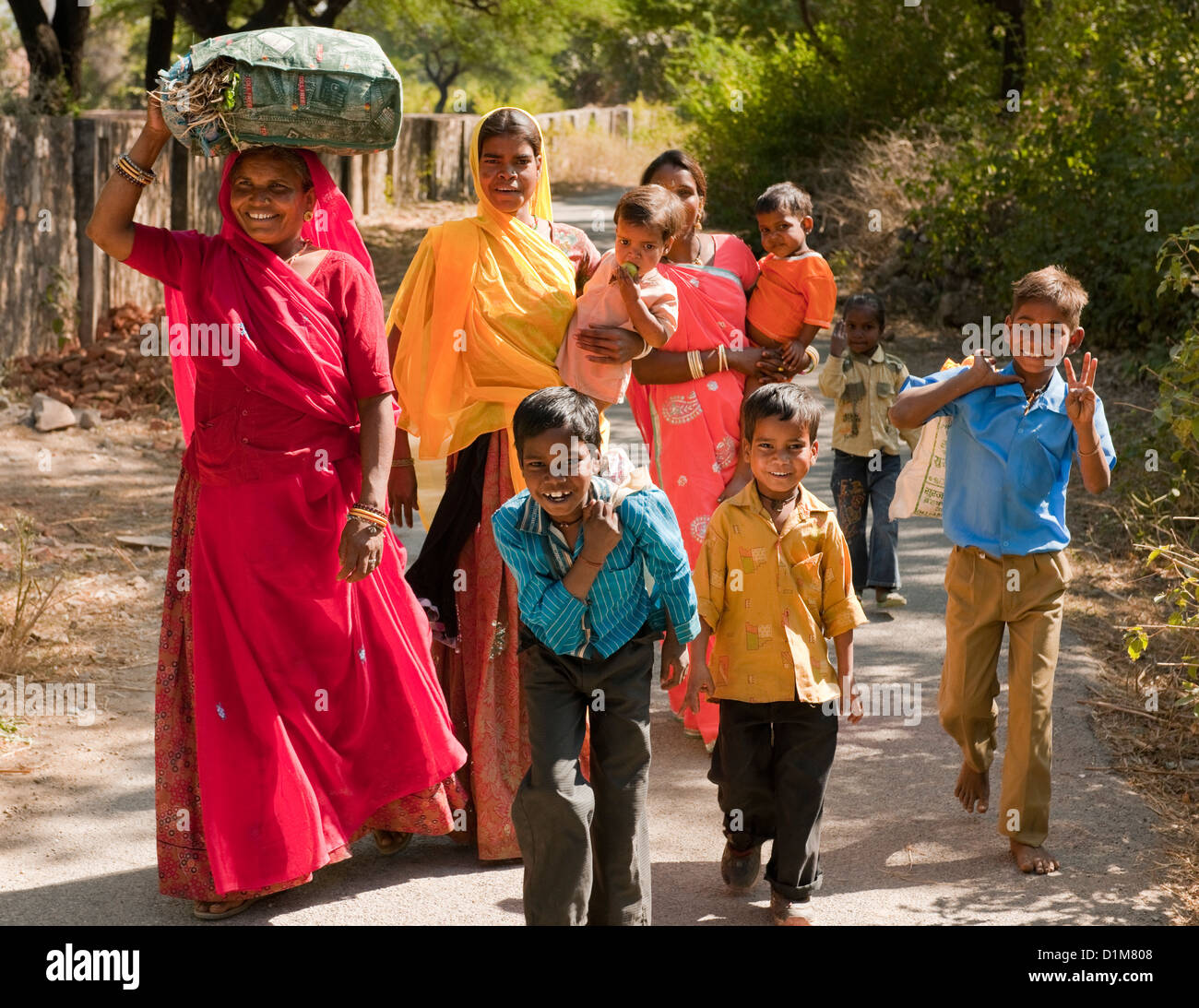 A happy smiling colorful Indian family group of women boys girls and a baby return from shopping on a quiet road Stock Foto