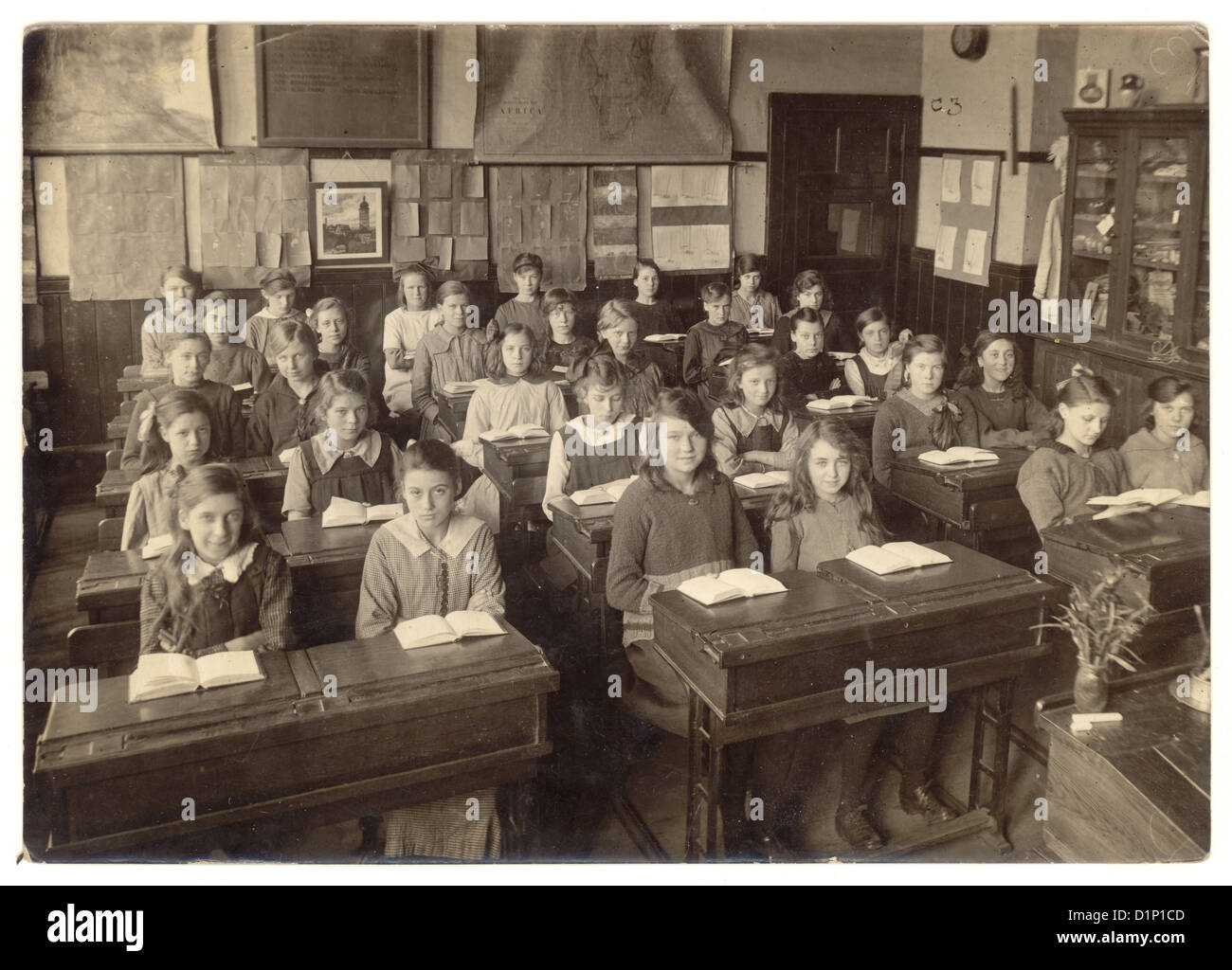 School photograph of junior girls sitting at their desks, with open books in classroom - 1930's, U.K. Stock Photo