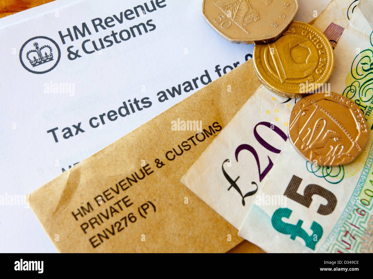 Close up of UK tax credits award from HM Revenue and Customs with brown official envelope and cash in coins and Stock Photo