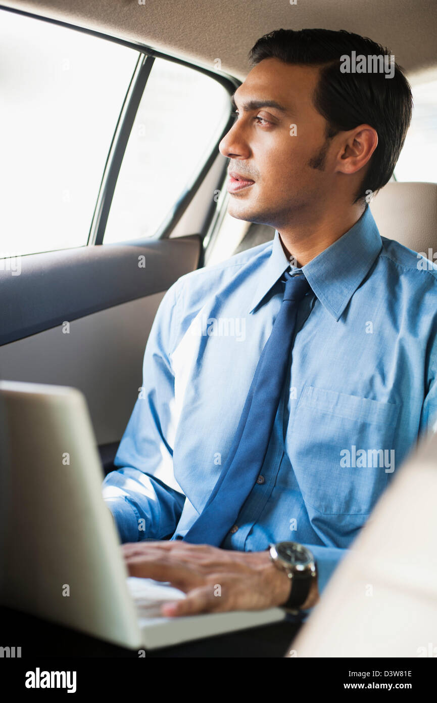 Bengali businessman using a laptop in a car Stock Foto