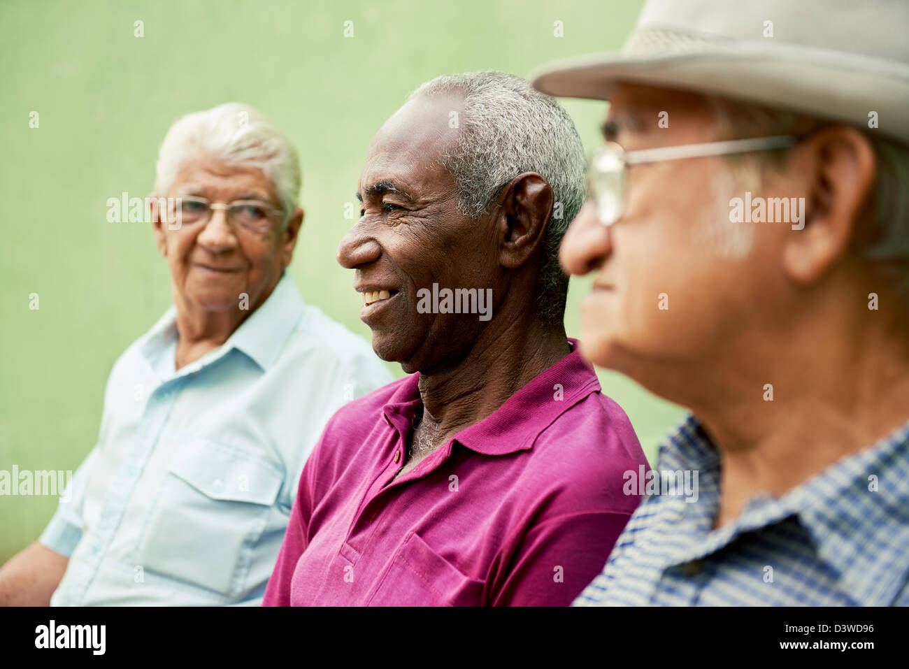 three senior men sitting on bench in park and talking Stock Foto