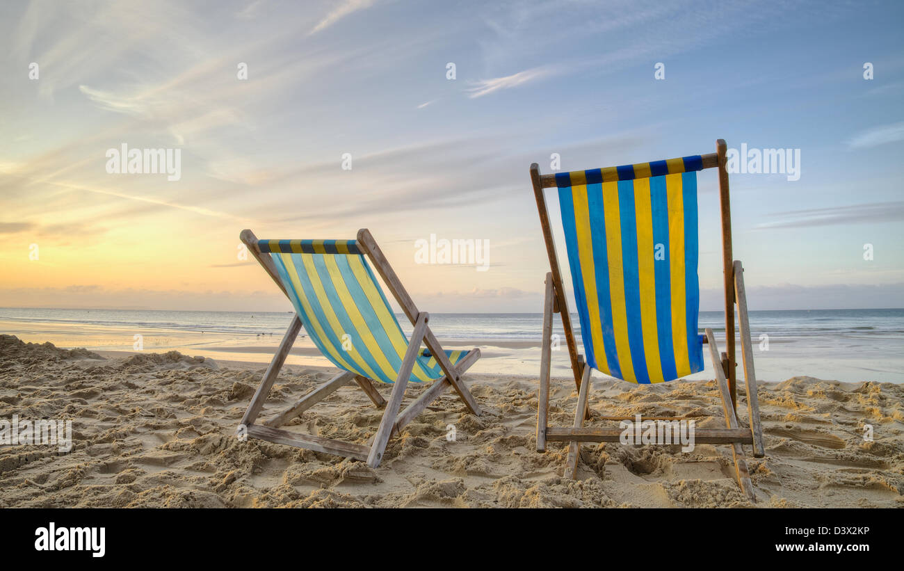 Two empty deck chairs on a beach at sunrise Stock Foto