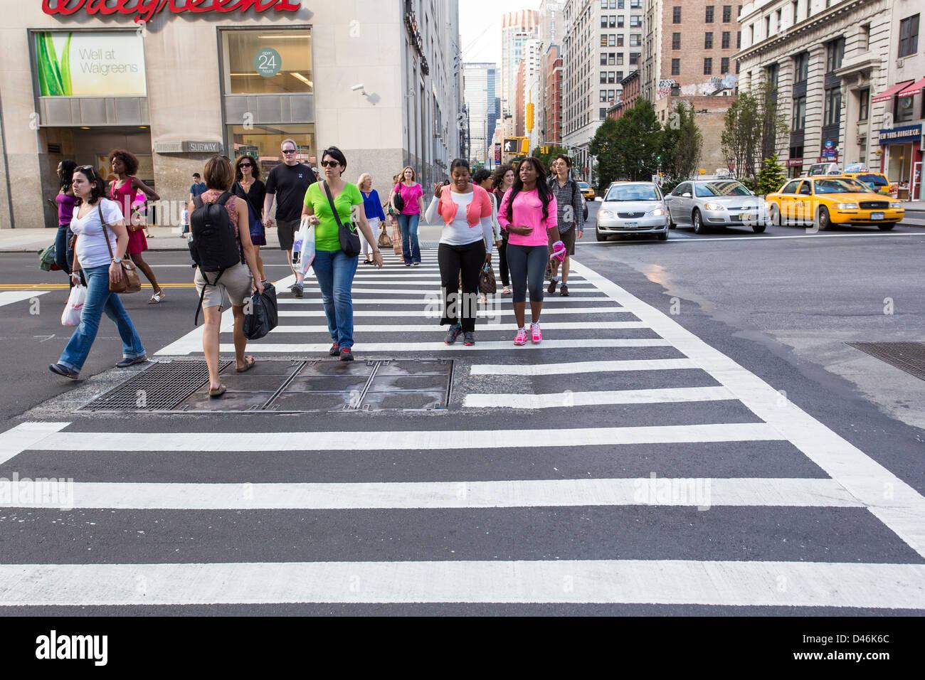 People crossing a street using a crosswalk in New York ...