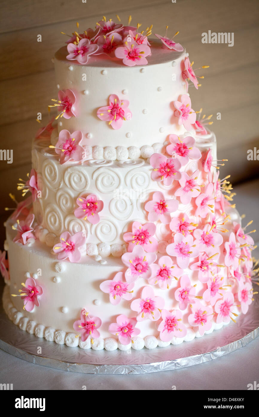 A White Three Tier Wedding Cake Decorated With Fuchsia Flowers Stock Photo Royalty Free Image