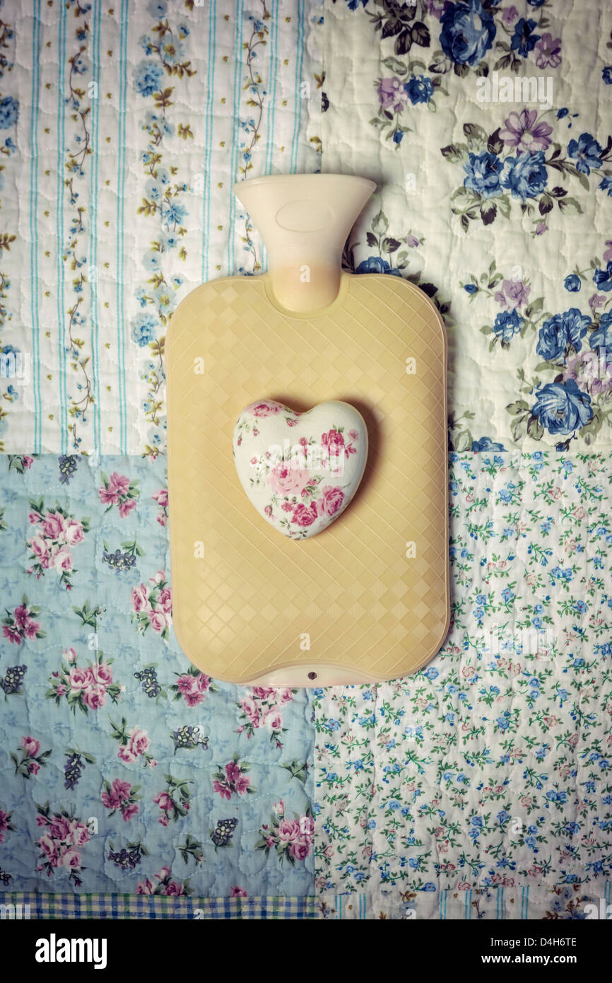 a hot-water bottle on a vintage bed with a floral heart Stock Foto