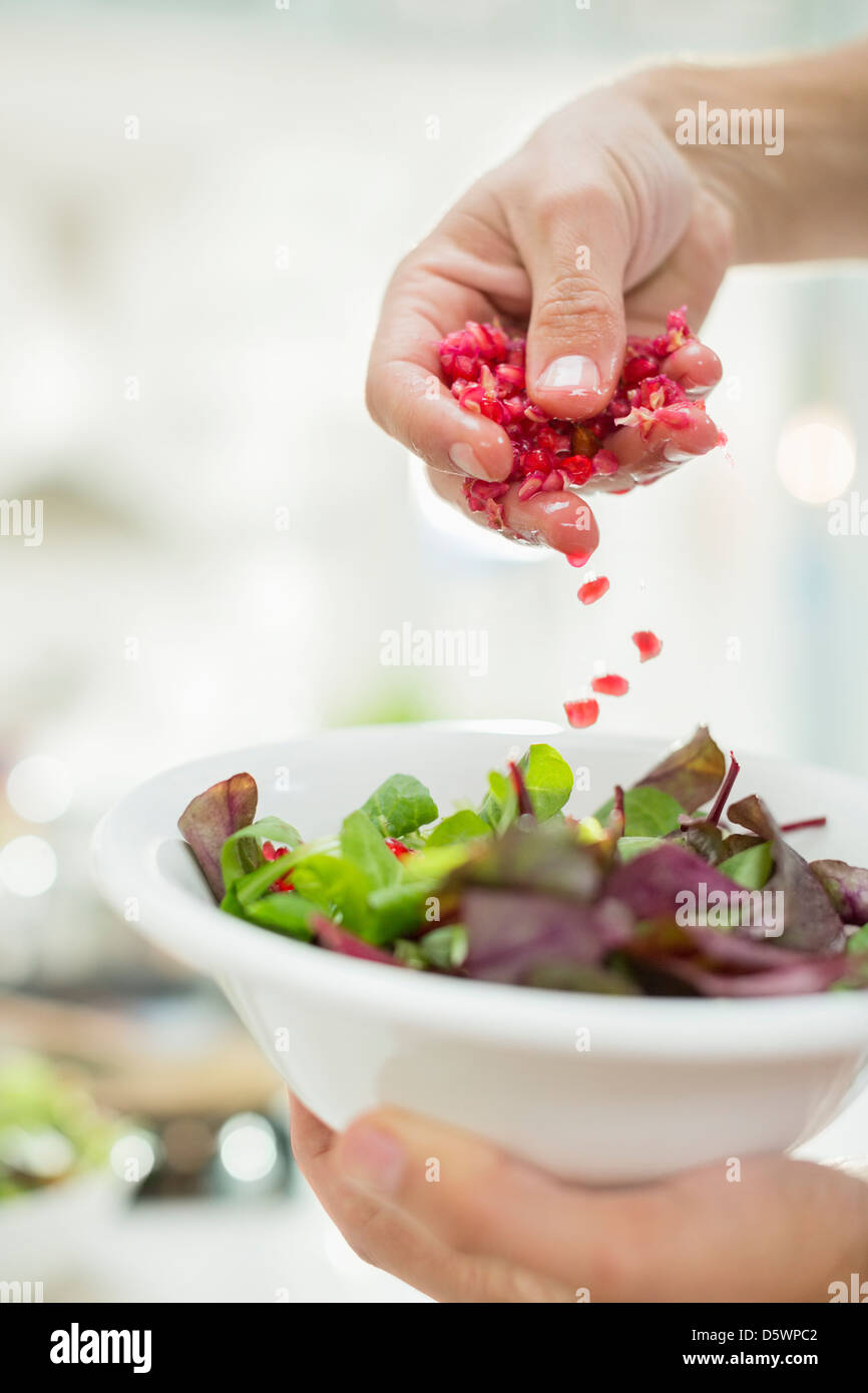 Woman making salad in kitchen Stock Foto