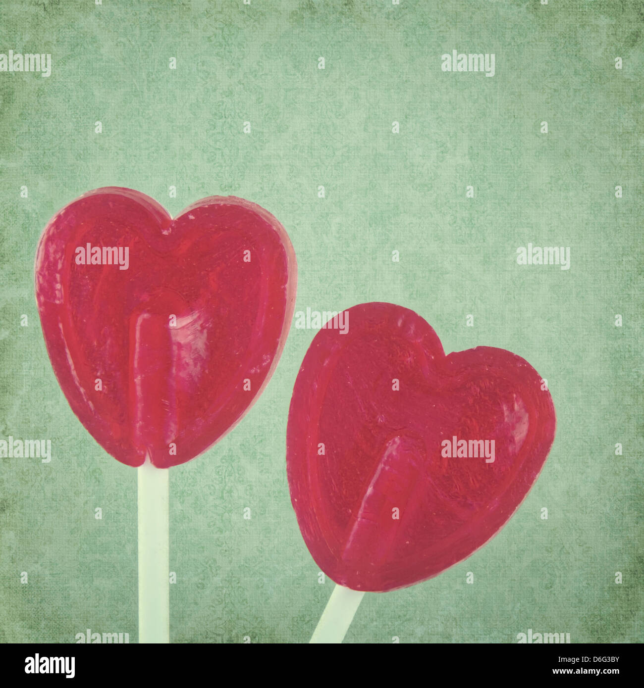 Red lollipop hearts on green vintage background Stock Foto