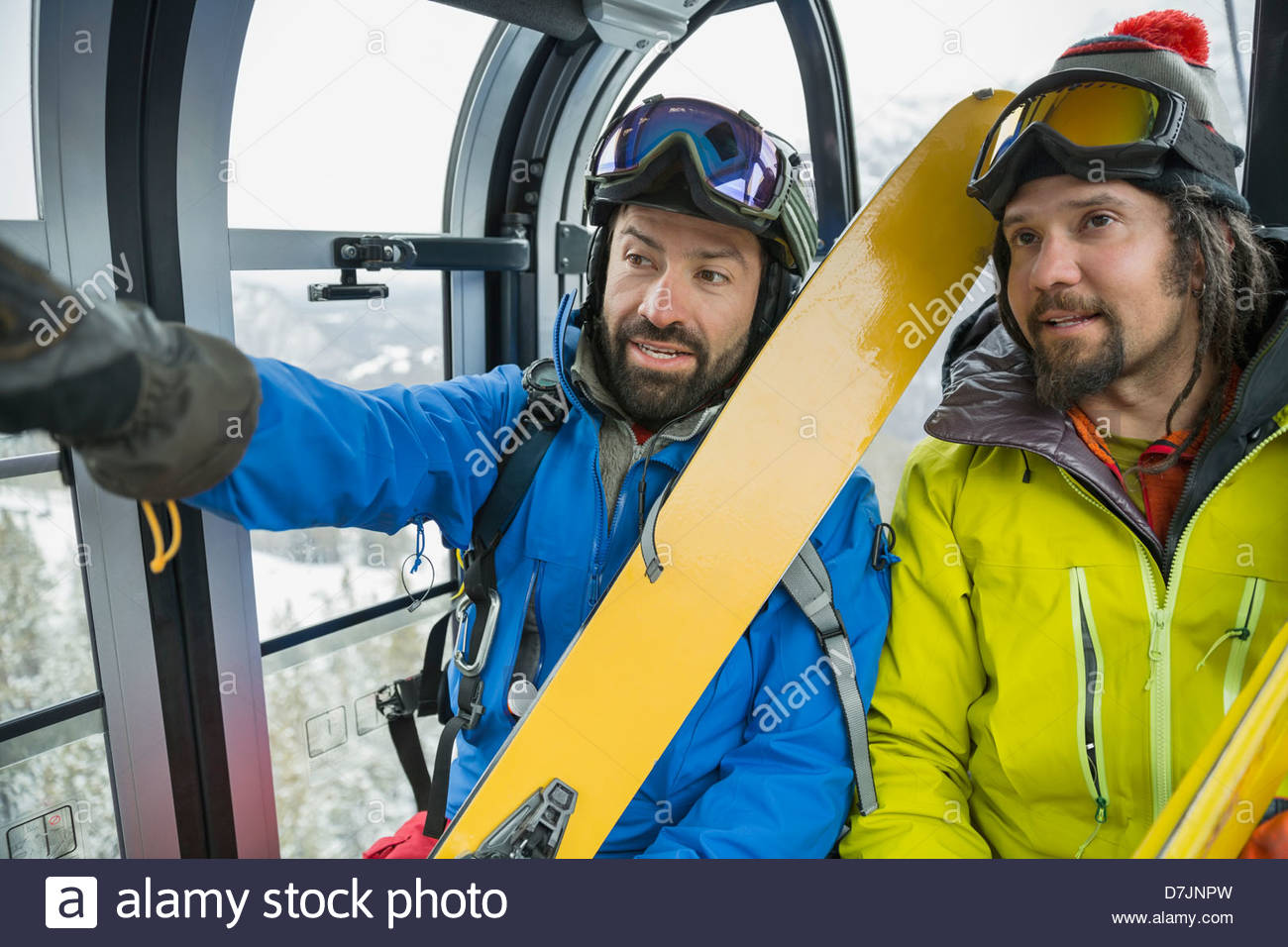 Male skiers talking in gondola in mountains Stock Photo