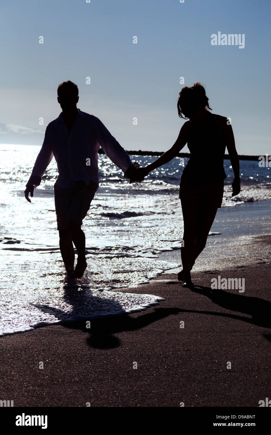 couple-running-on-beach-silhouetted-hand