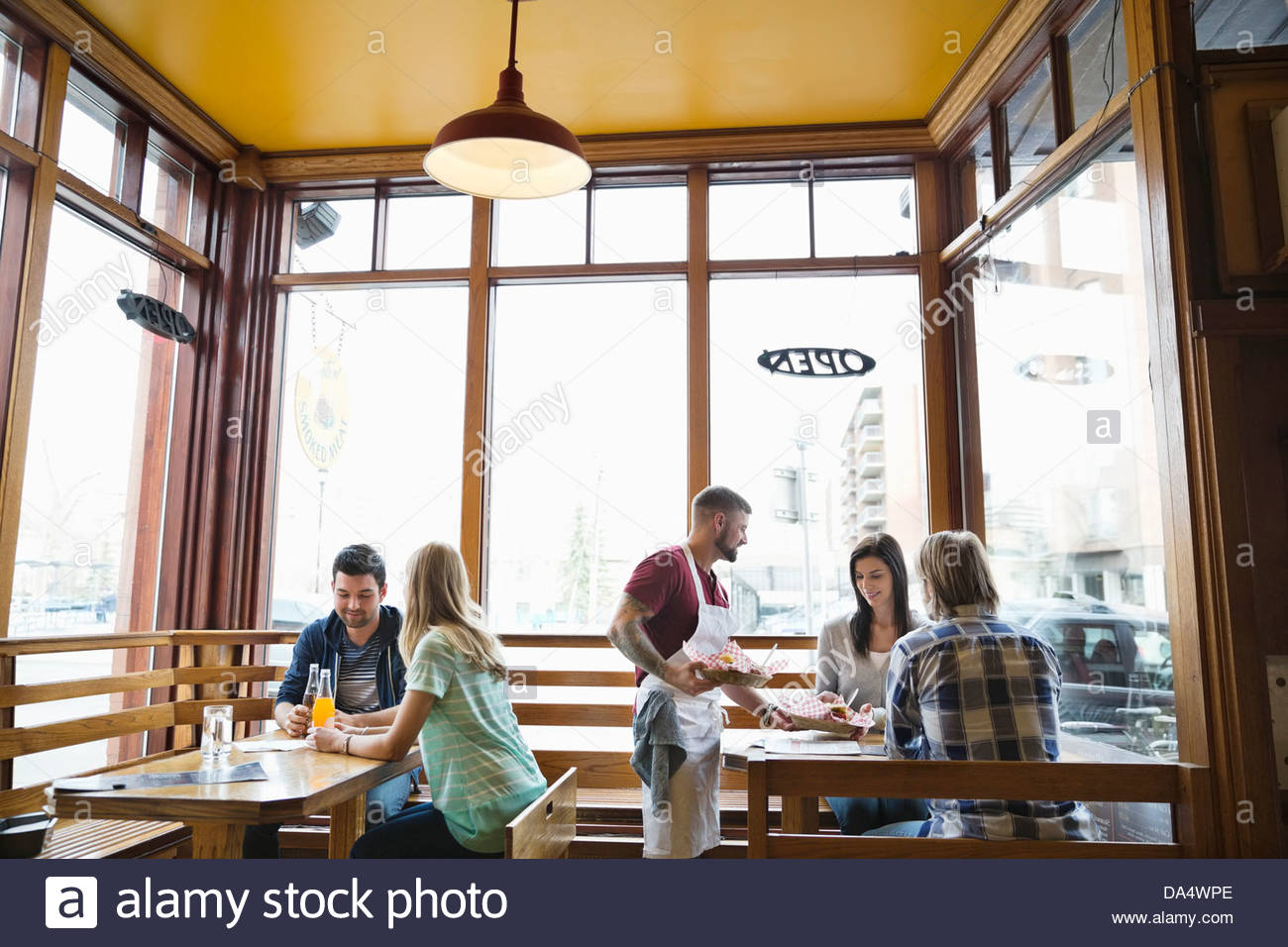 Male deli owner serving food to customers Stock Foto