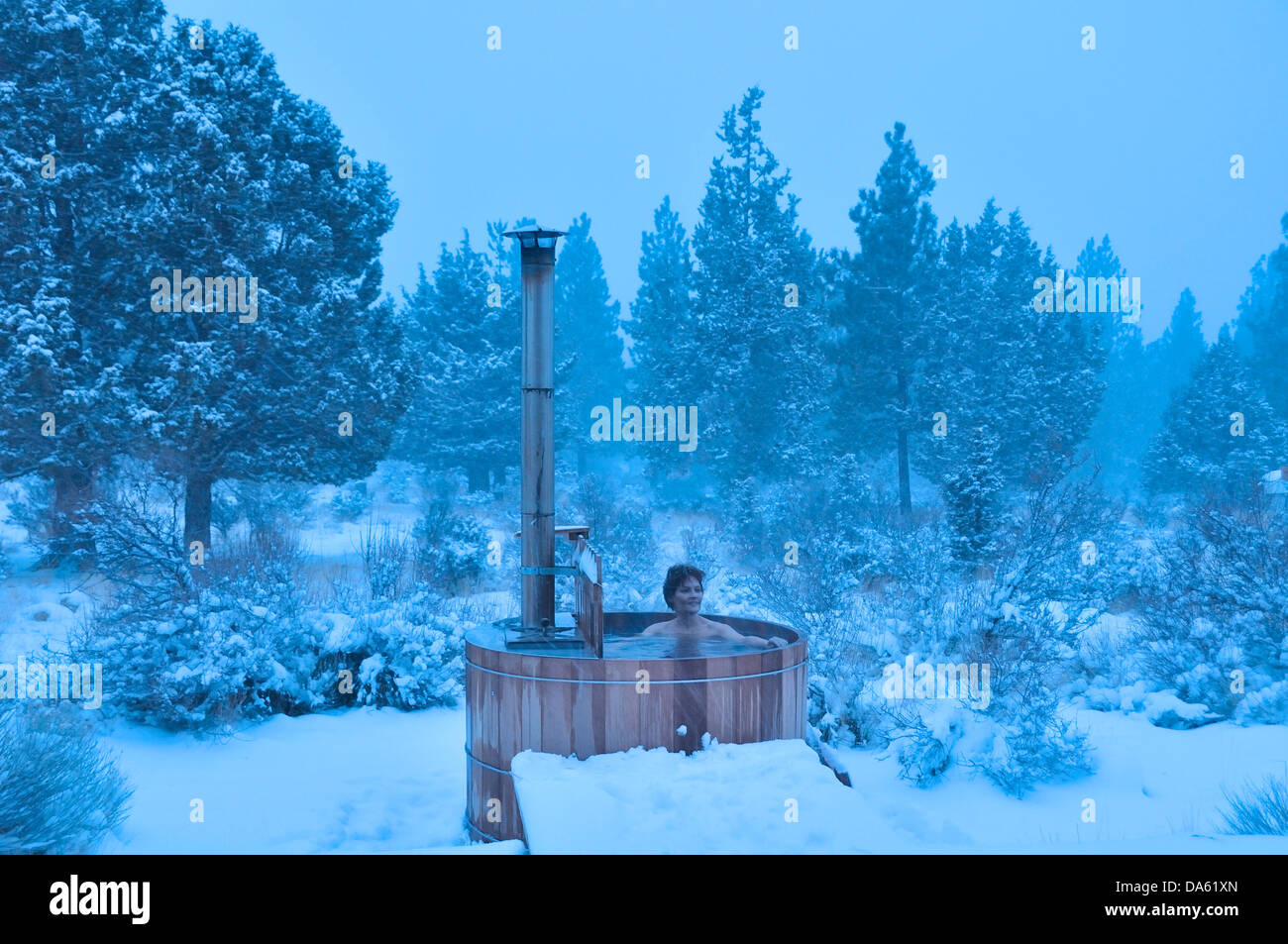 woman wood fired hot tub snow winter snowing central oregon stock photo royalty free. Black Bedroom Furniture Sets. Home Design Ideas