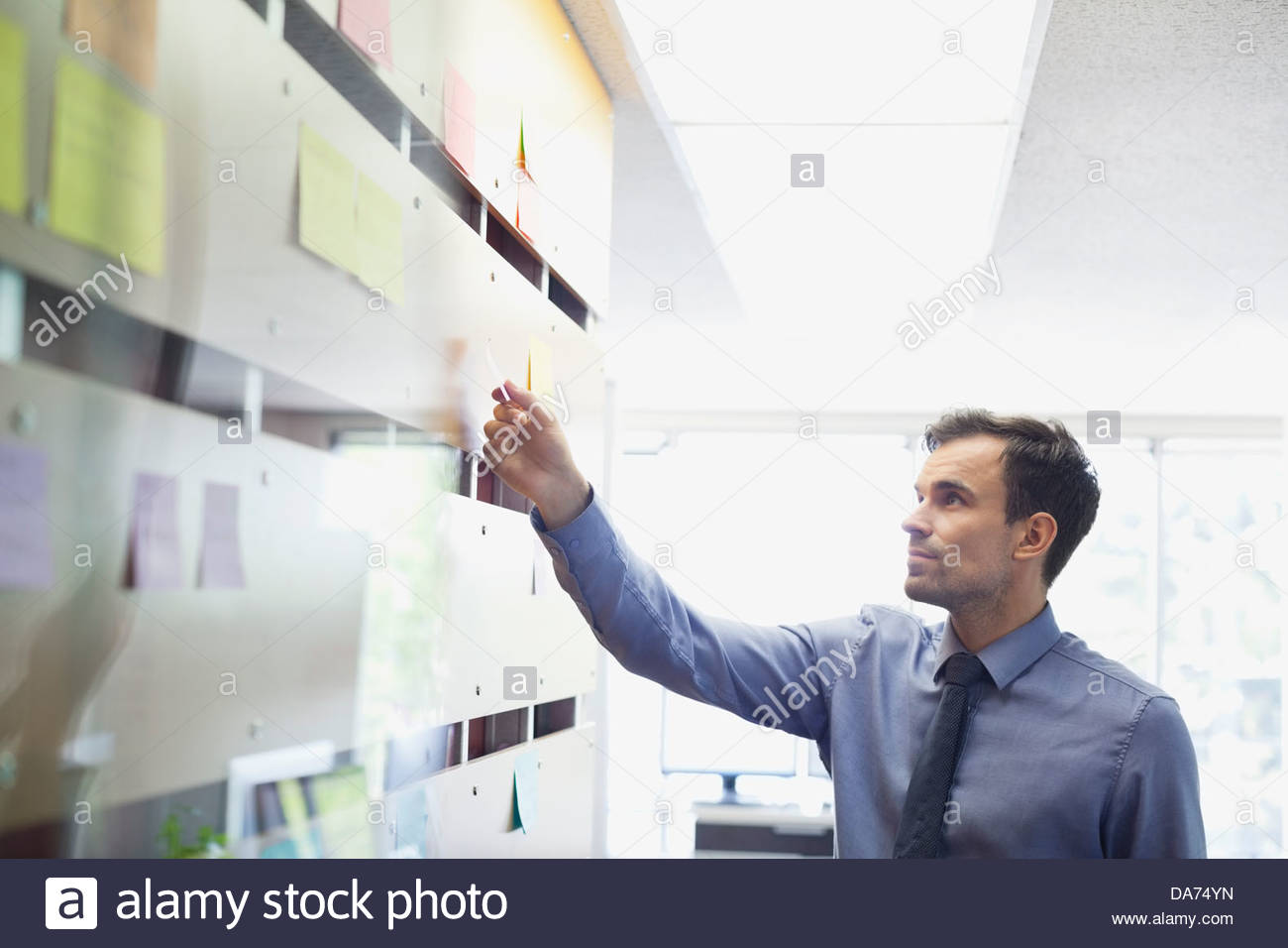 Businessman putting sticky note on wall Stock Foto