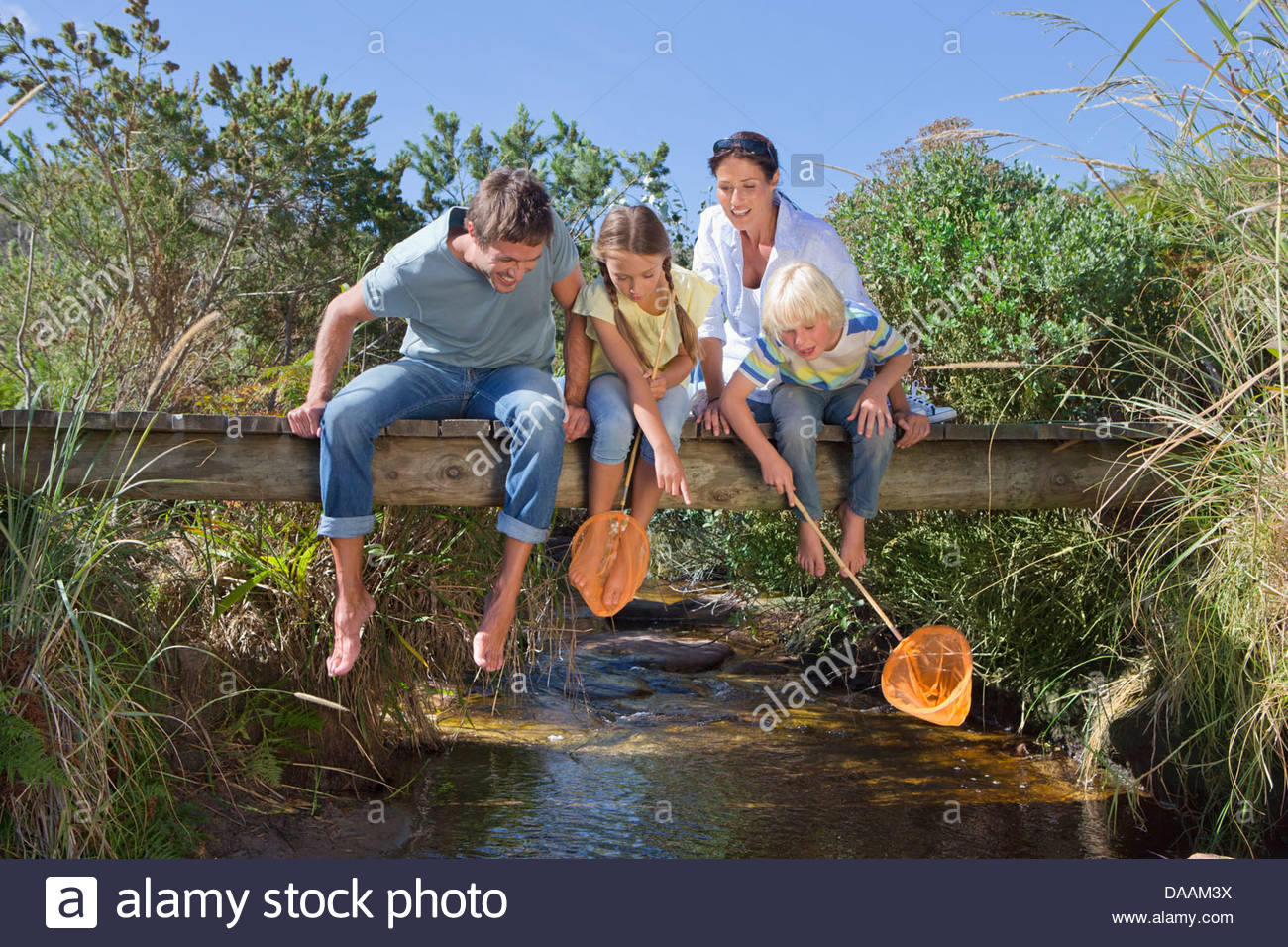 http://c7.alamy.com/comp/DAAM3X/family-with-fishing-nets-sitting-barefoot-on-footbridge-and-looking-DAAM3X.jpg