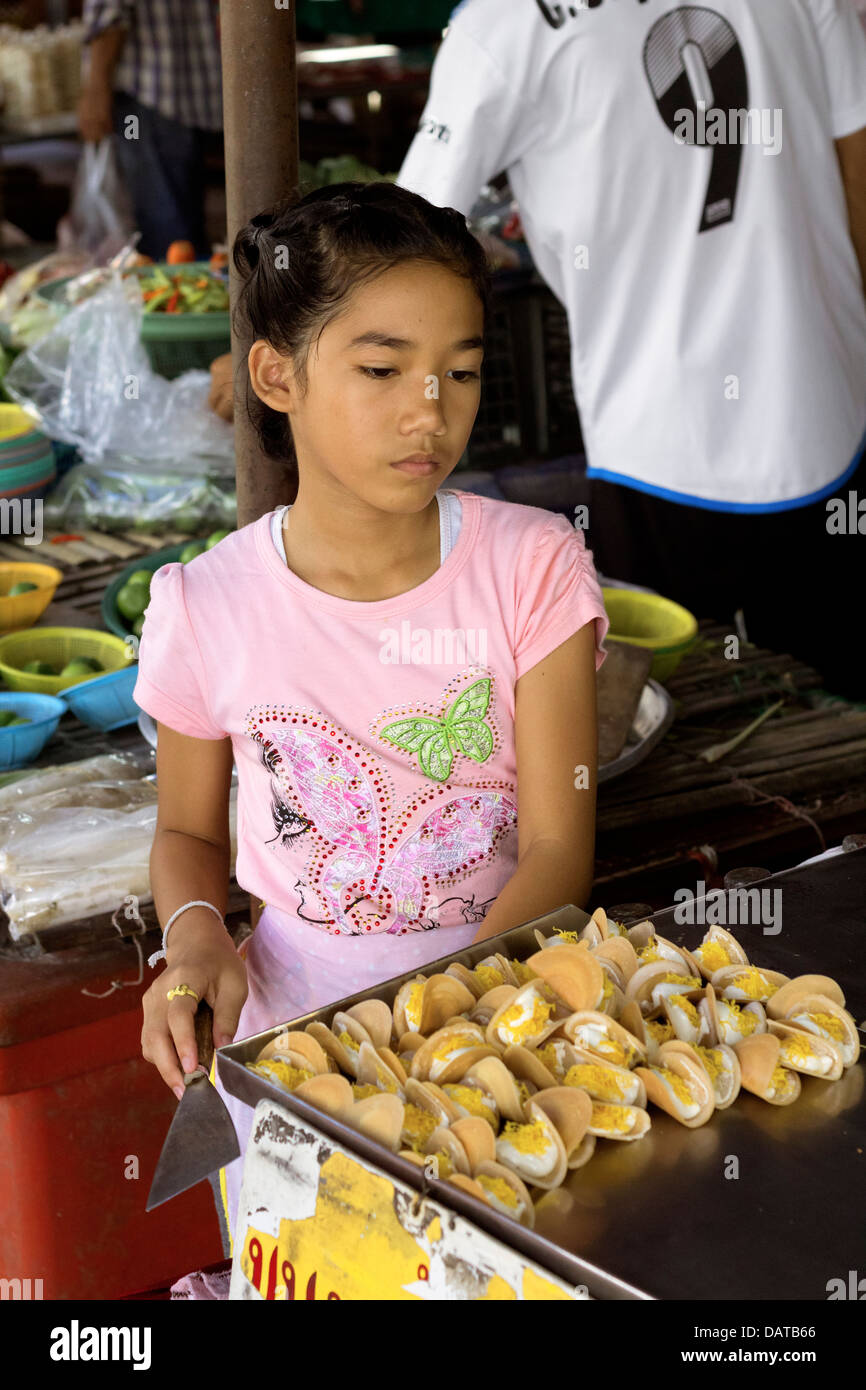 Young girl pan fries small thai pastries at market stall for Tiny thai teen