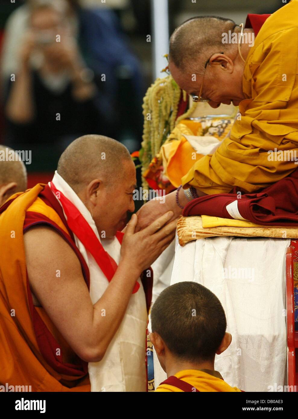 A monk gets in touch with the Dalai Lama (R) on his throne in Hamburg, Germany, 27 July 2007. The 72-year-old Nobel Stock Foto