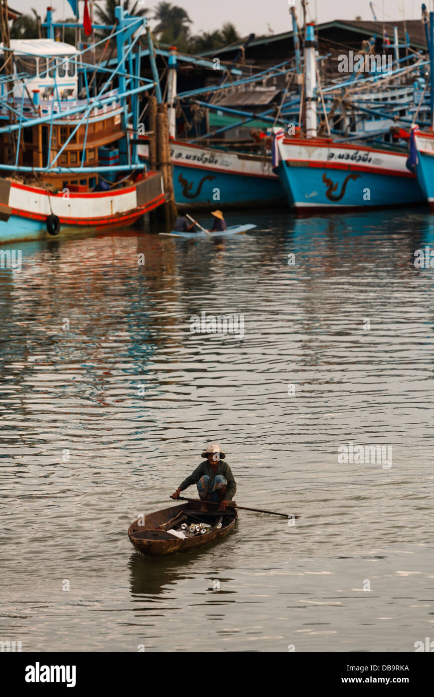 Two natives paddle small flat low narrow boats around the for Fishing paddle boats