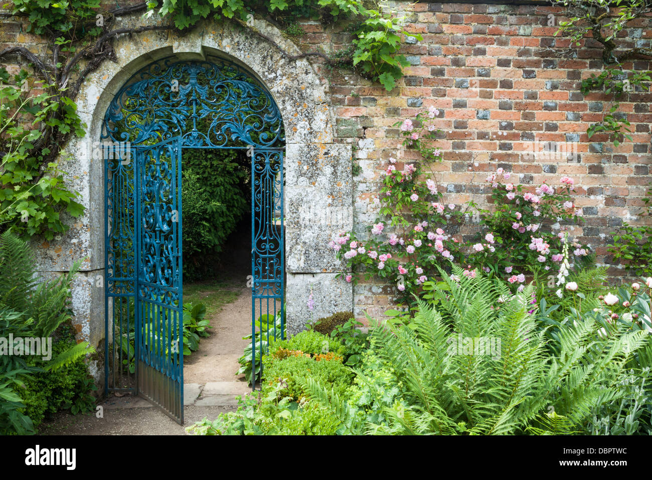 Ornate Wrought Iron Gate Set Within A Cotswold Stone Arch
