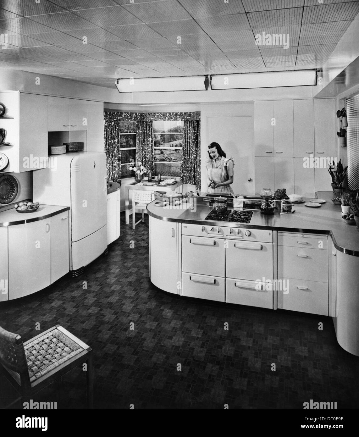 1950s HOUSEWIFE WORKING IN MODERN ELECTRIC KITCHEN Stock Foto
