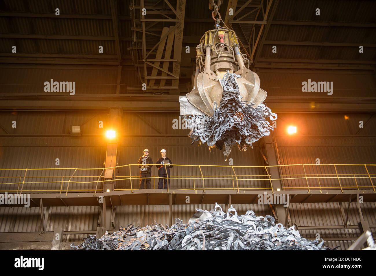 Steel workers watching mechanical grabber in steel foundry Stock Foto