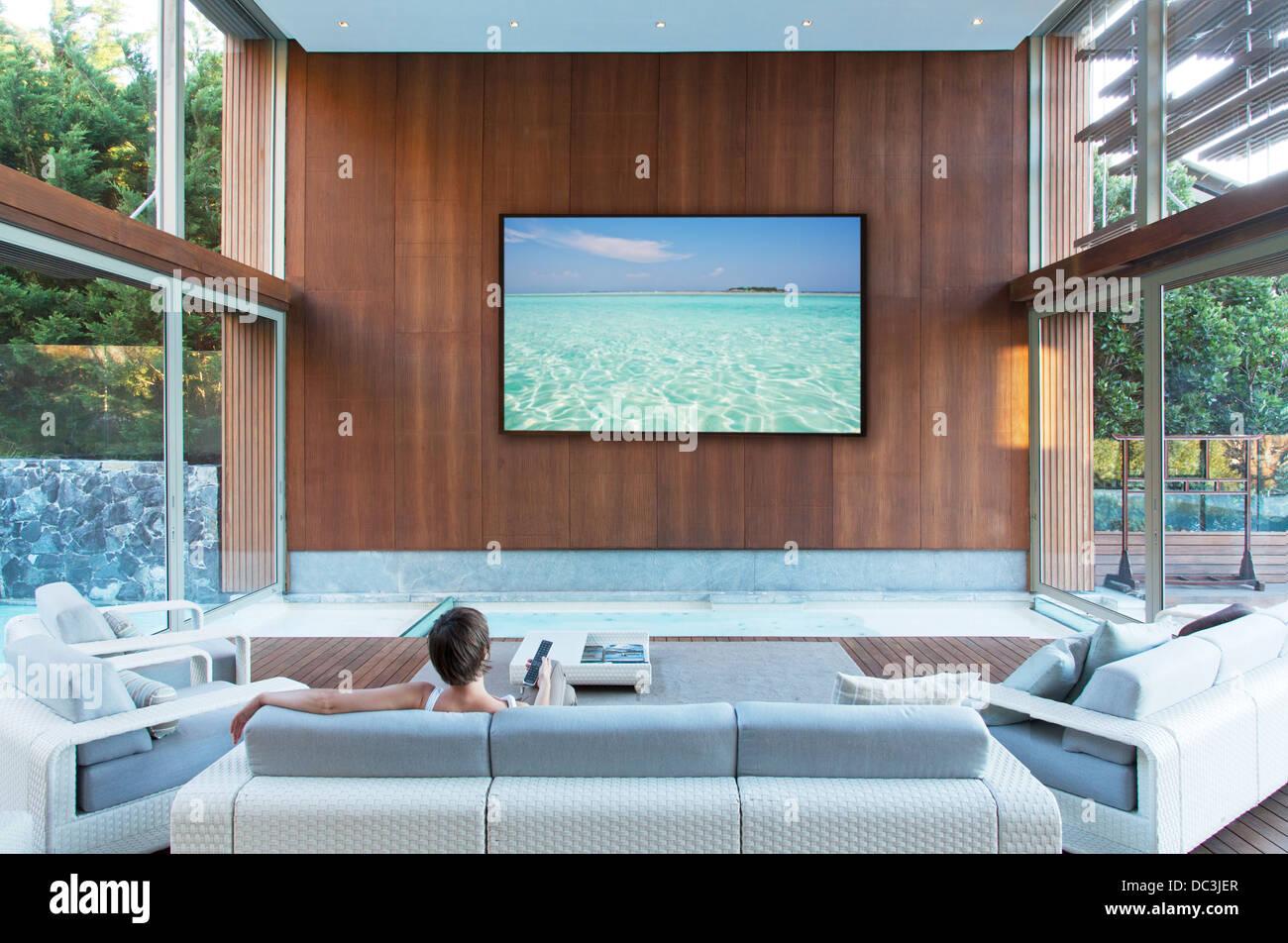 Woman watching large flat screen TV in modern living room ...
