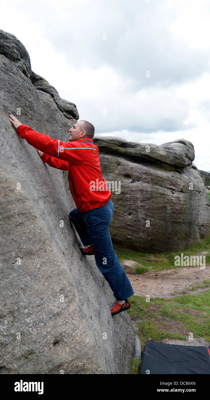rock climber Doug Blane bouldering at Burbage Edge South, Derbyshire, Peak District National Park, England, UK Stock Photo