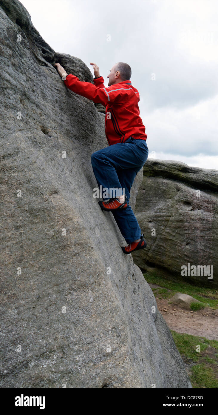rock climber Doug Blane bouldering at Burbage Edge South, Derbyshire, Peak District National Park, England, UK, Stock Photo