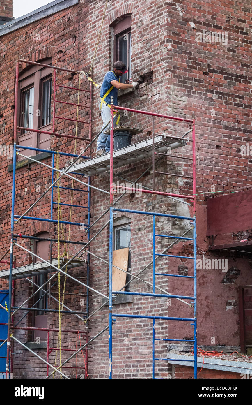 a brick mason works on a scaffolding three stories high to