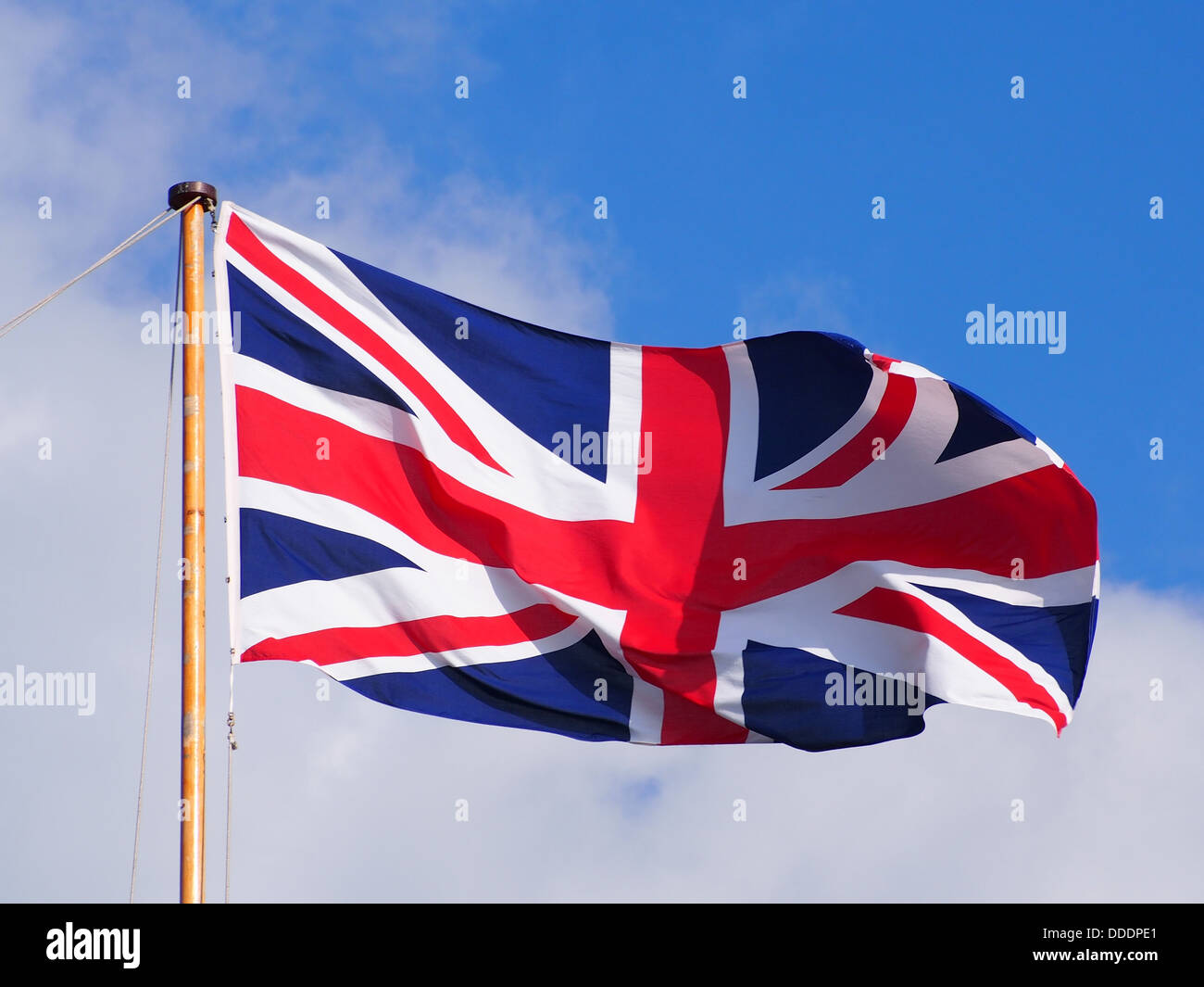 a-union-flag-flying-at-the-top-of-a-flagpole-against-a-partly-cloudy-DDDPE1.jpg