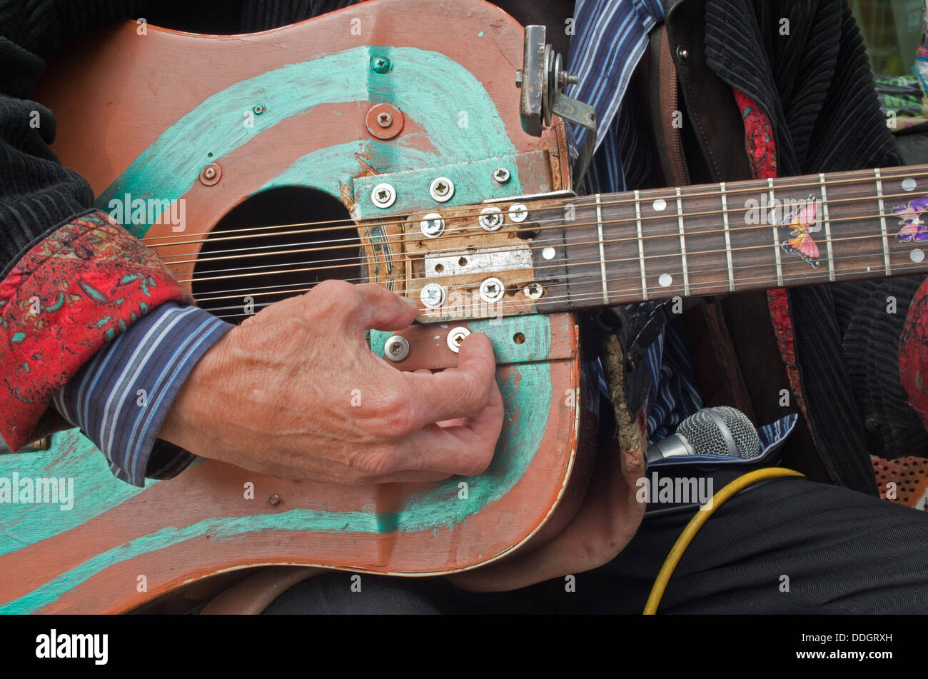 man-playing-a-repaired-hand-painted-guit