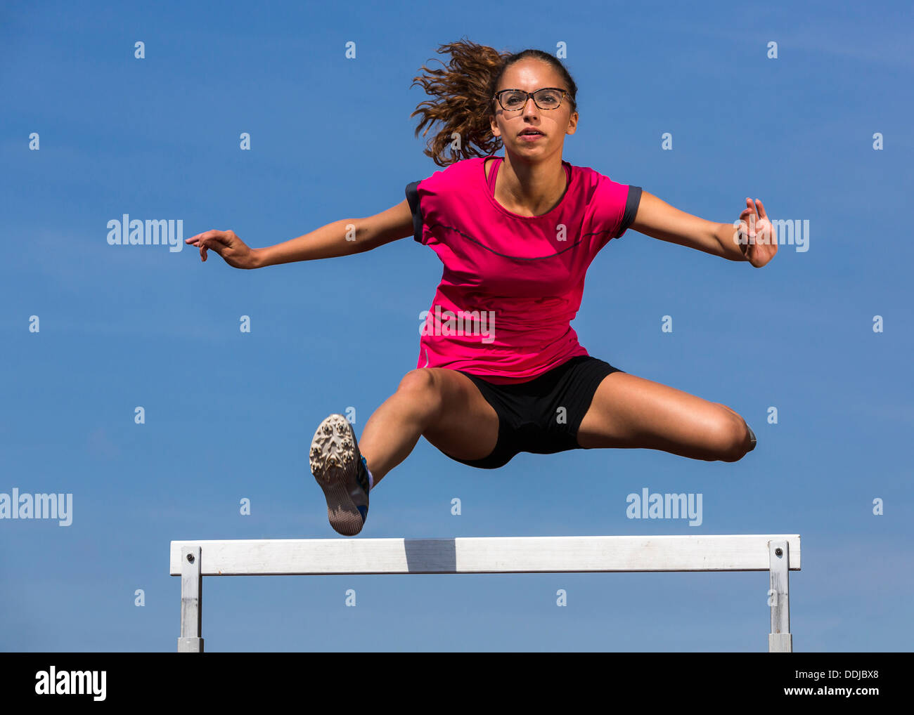 germany young woman athlete jumping hurdles on track stockfoto lizenzfreies bild 60026128 alamy. Black Bedroom Furniture Sets. Home Design Ideas