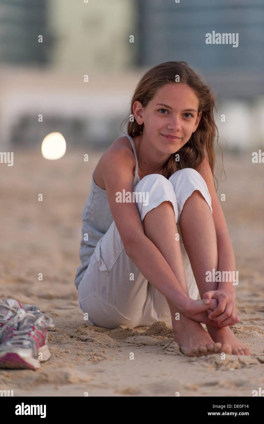 Preteen girl sitting on beach with barefeet, hugging knees ...: http://www.alamy.com/stock-photo-preteen-girl-sitting-on-beach-with-barefeet-hugging-knees-60248080.html